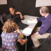 Three people sitting at a table with a laptop, talking