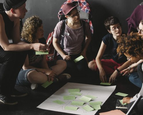 Group of 7 people squatting and sitting around a flipchart on the ground, mid conversation