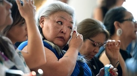 older indigenous woman seated, wiping tears.