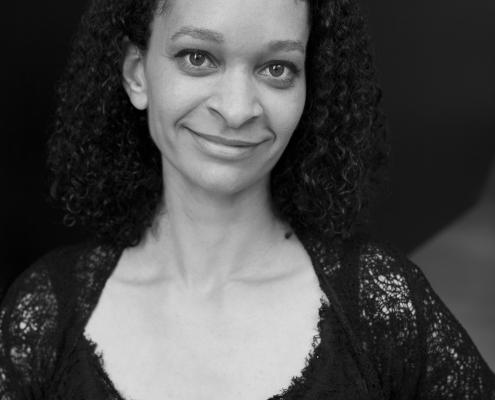 Portrait noir et blanc de Naïma qui sourit calmement.