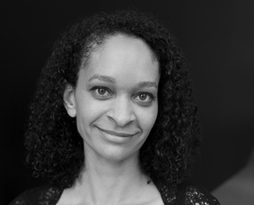 Greyscale portrait of Naïma calmly smiling into the camera.